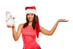 Woman with empty hand in santa hat holds snowman. Royalty Free Stock Image
