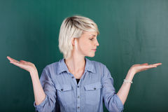 Woman With Empty Palms Against Chalkboard Stock Images