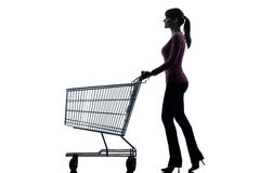 Woman with empty shopping cart silhouette. One caucasian woman with empty shopping cart in silhouette studio isolated on white background Royalty Free Stock Photography