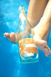 Woman with empty wine bottle. In pool Stock Photography