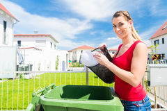 Woman emtying trash into litter box Royalty Free Stock Image