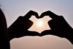 Woman&en x27; s-handen - gjorde en hjärtaform, med solen som ner, i hemlighet går i mitt och himlen i aftonen arkivbild