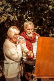 Woman encouraging her husband painting a landscape. Personal inspiration. Smiling elderly women encouraging her husband hugging him while he painting a royalty free stock photography