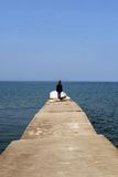 Woman at end of long pier. Rear view of woman stood at end of long pier with blue sea and sky background Stock Images
