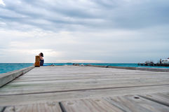Woman at end of pier closing eyes and looking up. A perspective shot of a woman sitting at the end of a pier, looking up Royalty Free Stock Photography