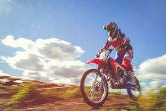 Woman on enduro motocross in motion, desire for victory, dynamics of speed stock image