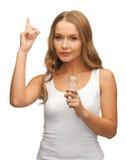 Woman with energy saving bulb Stock Images