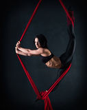 The woman is engaged in aerial acrobatics. Stock Images