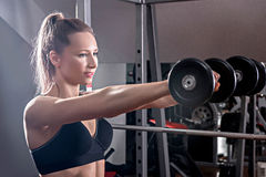 The woman is engaged with a dumbbell in the gym. The girl with d Stock Photography