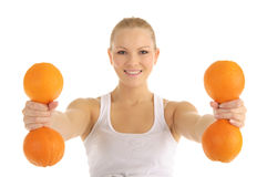 Woman engaged in fitness dumbbells of oranges Stock Photo
