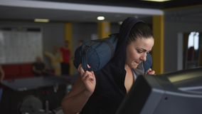 Woman is engaged in fitness on treadmill, she is holding a bag on her shoulders. stock video