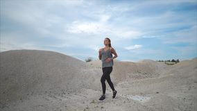 The woman is engaged in running on the nature, the sportswoman is exercising. A young woman in a sport suit runs along the sand park, an athlete makes exercises stock footage