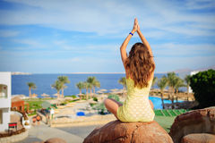 Woman is engaged in yoga on a background of the sea Royalty Free Stock Images