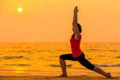Woman engaged in yoga at sunset Stock Photography