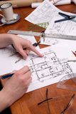 Woman engineer, architect or contractor works on plans. A woman engineer, architect or contractor working on and inspecting  blueprints or home plans Royalty Free Stock Photography