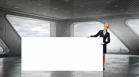 Woman engineer with banner . Mixed media. Attractive woman builder demonstrating white blank banner. Mixed media Royalty Free Stock Images