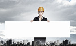 Woman engineer with banner . Mixed media. Attractive woman builder demonstrating white blank banner Stock Photos