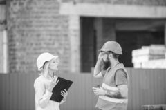 Woman engineer and bearded brutal builder discuss construction progress. Construction industry concept. Relationships royalty free stock image