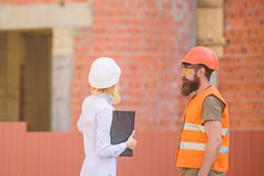 Woman engineer and bearded brutal builder discuss construction progress. Discuss progress plan. Construction industry stock image