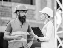 Woman engineer and bearded brutal builder discuss construction progress. Construction project management. Building stock photography