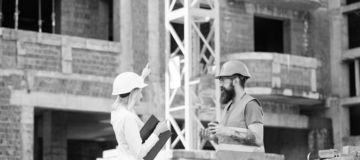 Woman engineer and brutal builder communicate construction site background. Relationships between construction clients stock photo