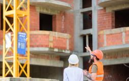 Woman engineer and builder communicate at construction site. Relationships between construction clients and participants. Building industry. Construction team stock images