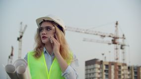 Woman engineer designer talking on the phone with the contractor with drawings in hand on the background of buildings. Under construction and cranes stock video