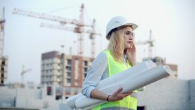 Woman engineer designer talking on the phone with the contractor with drawings in hand on the background of buildings. Under construction and cranes stock footage