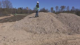 Woman engineer on gravel pile. In summer day stock video footage