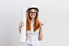 Woman engineer in a helmet and glasses keeps blueprints on a light background Royalty Free Stock Photo