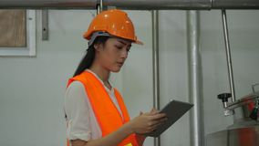 Woman engineer looking at computer tablet and checking data on the tablet