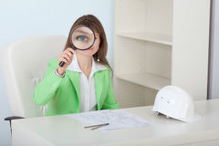 Woman engineer looks at us through magnifier Stock Image