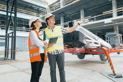 Woman engineer and man builder at construction site. Building, development, teamwork and people concept. Woman engineer and men builder at construction site stock photography