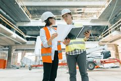 Woman engineer and man builder at construction site. Building, development, teamwork and people concept. Woman engineer and men builder at construction site royalty free stock images