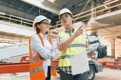 Woman engineer and man builder at construction site. Building, development, teamwork and people concept. Woman engineer and men builder at construction site stock photos