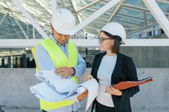 Woman engineer and man builder at construction site. Building, development, teamwork and people concept royalty free stock image