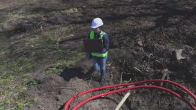 Woman engineer near cables in plastic pipes. In summer day stock footage