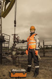 Woman engineer in the oil field. With the wrench and toolbox wearing orange helmet and work clothes. Pump jack background. Oil and gas concept. Toned Stock Images