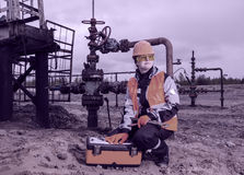 Woman engineer in the oil field. With the wrench and toolbox wearing orange helmet and work clothes. Pump jack and wellhead background. Oil and gas concept Royalty Free Stock Photo