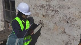 Woman engineer at the old wall. In summer day stock video footage