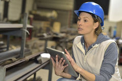 Woman engineer with a security helmet in steel plant using tablet Stock Photography