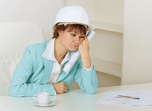 Woman engineer sits on workplace at office. The woman the engineer sits on a workplace at office and mourns royalty free stock photos