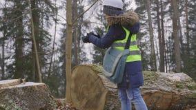 Woman engineer using lightweight video camera near stump in snowfall