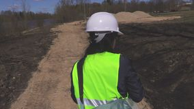 Woman engineer walking and talks about construction site. In summer day stock video footage