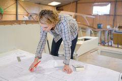 Woman engineer working on blueprint at site. Drawings stock images