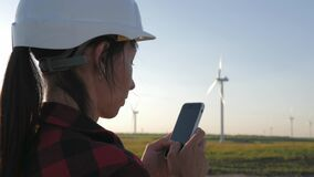 Free Woman Engineer Working In Wind Turbine Electricity Industrial At Sunset. Stock Photo - 195789320