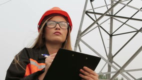 Woman engineer working near an electrical substation lines, power lines, teamwork. Female engineer working near an electrical substation lines, power lines stock footage