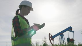 Woman engineer writing on clipboard in oil field. Female wearing white helmet and work clothes. Industrial, oil and gas stock footage