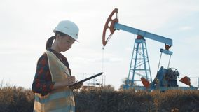 Woman engineer writing on clipboard in oil field. Female wearing white helmet and work clothes. Industrial, oil and gas stock video footage