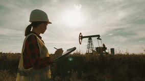 Woman engineer writing on clipboard in oil field. Female wearing white helmet and work clothes. Industrial, oil and gas stock video